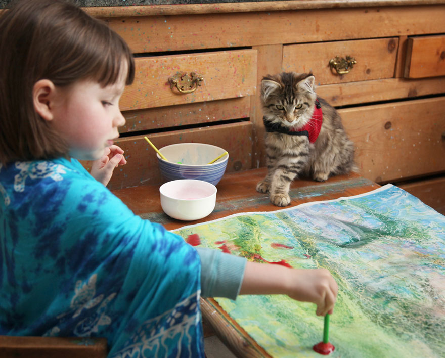 Young child paints while a kitty watches.